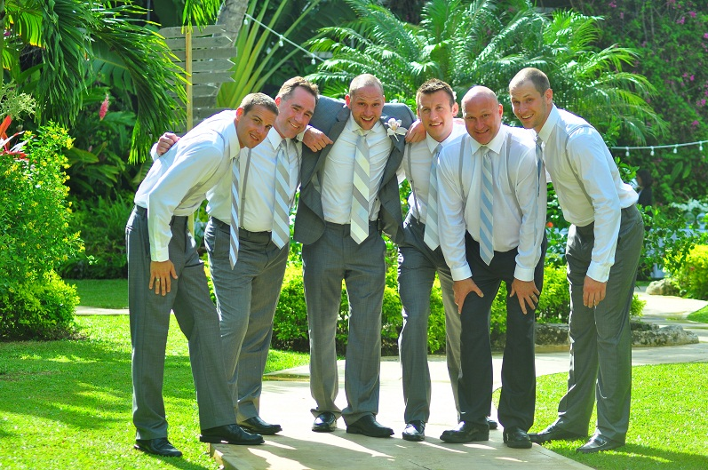Group of groomsmen sporting festive ties and smiles surrounded by green botanical garden